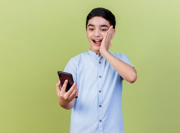 Onder de indruk jonge jongen die en mobiele telefoon houdt bekijkt die hand op gezicht houdt dat op olijfgroene muur wordt geïsoleerd