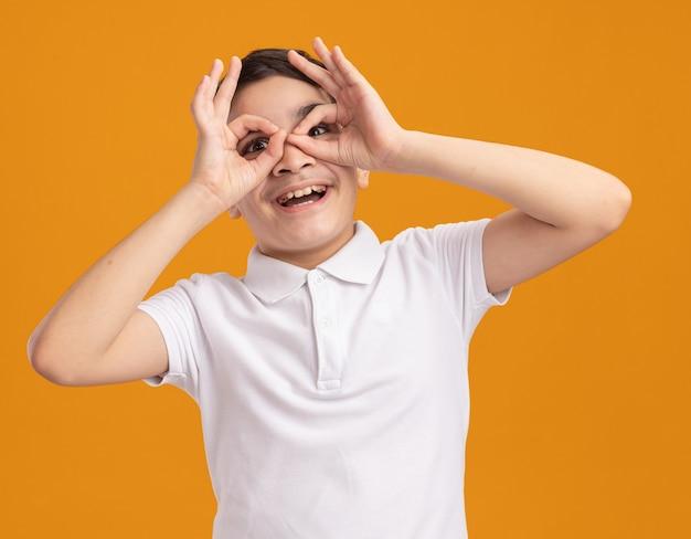 Onder de indruk jonge jongen die naar de voorkant kijkt en een gebaar doet met zijn handen als verrekijker geïsoleerd op een oranje muur
