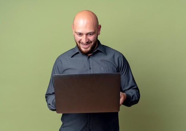 Onder de indruk jonge kale call center man houden en kijken naar laptop geïsoleerd op olijfgroen met kopie ruimte