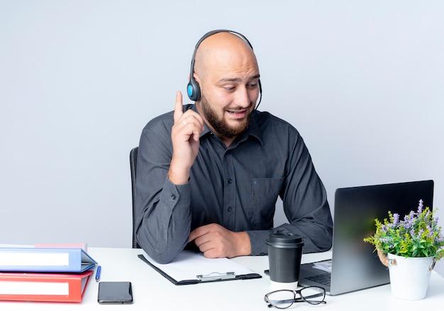 Onder de indruk jonge kale call center man met headset zit aan bureau met uitrustingsstukken kijken naar laptop en verhogen vinger geïsoleerd op wit