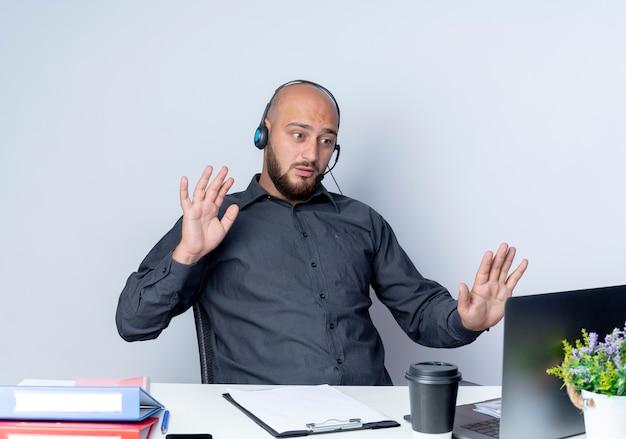 Onder de indruk jonge kale call center man met hoofdtelefoon zit aan bureau met werk tools kijken naar laptop en tonen lege handen stop gebaar doen op laptop geïsoleerd op wit