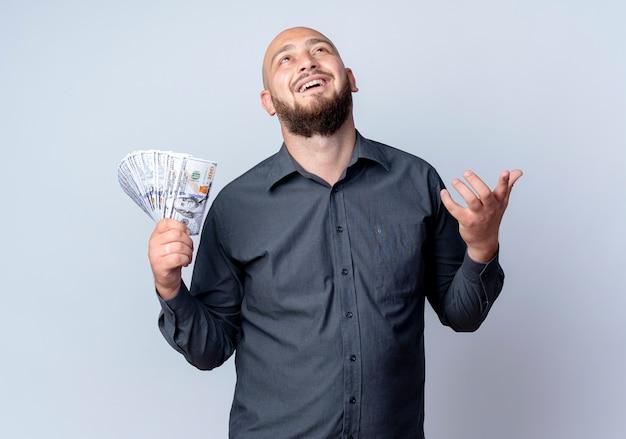 Onder de indruk jonge kale callcentermens met geld die lege hand toont en omhoog geïsoleerd op wit kijkt