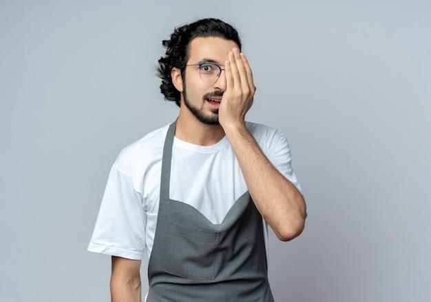 Onder de indruk jonge kaukasische mannelijke kapper bril en golvende haarband dragen uniform die betrekking hebben op de helft van het gezicht met hand geïsoleerd op een witte achtergrond met kopie ruimte