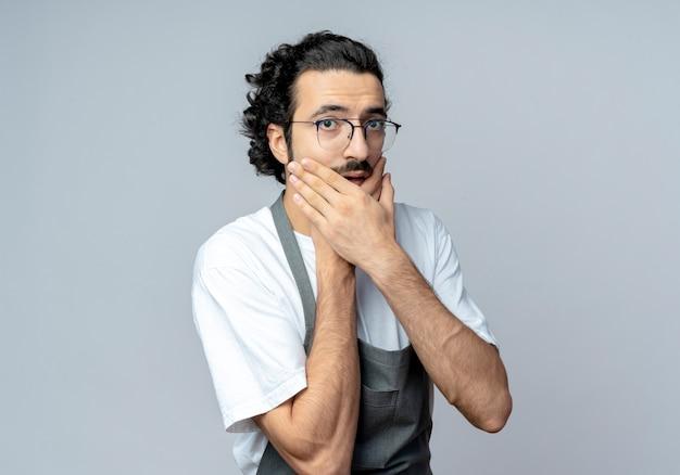 Onder de indruk jonge kaukasische mannelijke kapper bril en golvende haarband dragen uniform handen op kin geïsoleerd op een witte achtergrond met kopie ruimte