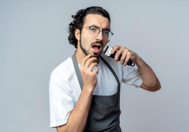 Onder de indruk jonge kaukasische mannelijke kapper bril en golvende haarband dragen uniform zijn baard trimmen met een tondeuse en aanraken van zijn kin geïsoleerd op een witte achtergrond met kopie ruimte