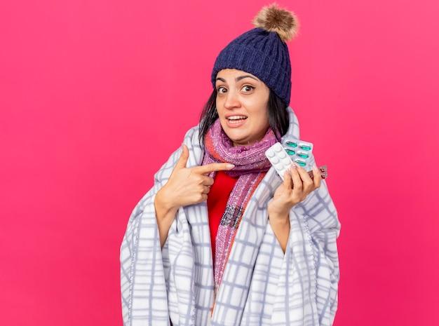Onder de indruk jonge kaukasische ziek meisje dragen winter hoed en sjaal verpakt in geruite bedrijf en wijzend op verpakkingen van medische pillen kijken camera geïsoleerd op crimson achtergrond met kopie ruimte