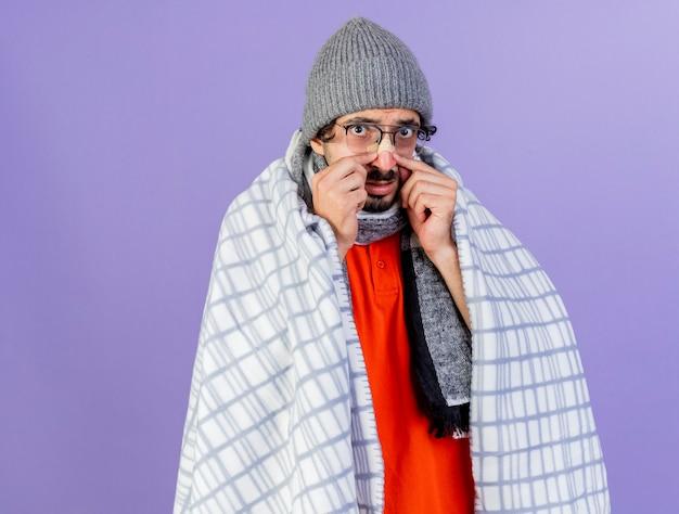 Onder de indruk jonge kaukasische zieke man met bril, muts en sjaal gewikkeld in plaid kijken camera gips zetten neus geïsoleerd op paarse achtergrond met kopie ruimte