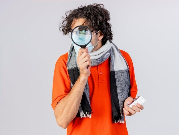 Onder de indruk jonge kaukasische zieke man met bril, sjaal en masker houden van medische pillen camera kijken door vergrootglas geïsoleerd op een witte achtergrond met kopie ruimte