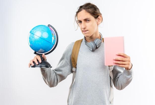 Onder de indruk jonge kerel student draagt rugzak met koptelefoon op nek met globe met notebook geïsoleerd op een witte muur