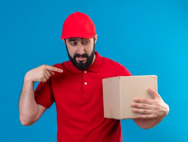 Onder de indruk jonge knappe blanke bezorger met rode uniform en pet bedrijf kijken en wijzend op kartonnen doos geïsoleerd op blauw
