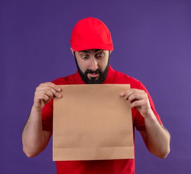 Onder de indruk jonge knappe blanke bezorger met rode uniform en pet houden en kijken naar papieren pakket geïsoleerd op paars