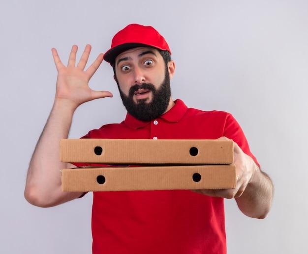 Onder de indruk jonge knappe blanke bezorger met rode uniform en pet houden en kijken naar pizzadozen met opgeheven hand geïsoleerd op wit