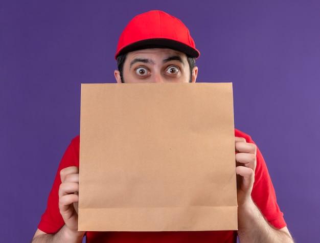 Onder de indruk jonge knappe blanke bezorger met rode uniform en pet op zoek van achter papieren pakket geïsoleerd op paars