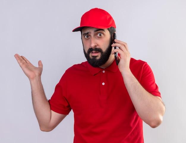 Onder de indruk jonge knappe blanke bezorger met rode uniform en pet praten over de telefoon en lege hand tonen op wit wordt geïsoleerd