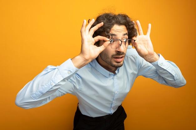 Onder de indruk jonge knappe blanke man dragen en grijpen bril kijken kant geïsoleerd op een oranje achtergrond