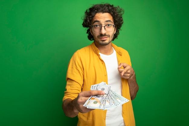 Onder de indruk jonge knappe blanke man met bril geld uitrekken wijzend op het geïsoleerd op groene muur met kopie ruimte