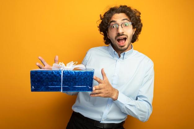 Onder de indruk jonge knappe blanke man met bril houden geschenkverpakking kijken camera geïsoleerd op een oranje achtergrond