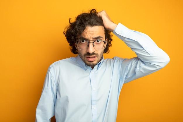 Onder de indruk jonge knappe blanke man met bril kijken camera grijpen haar geïsoleerd op een oranje achtergrond