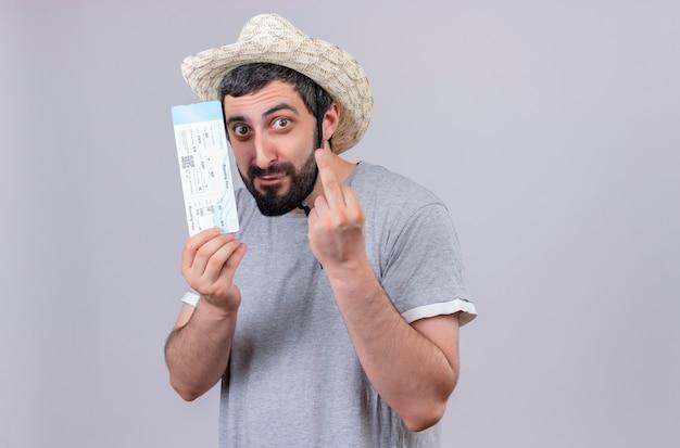 Onder de indruk jonge knappe blanke reiziger man met hoed en vliegtuigticket te houden en middelvinger gebaar geïsoleerd op wit met kopie ruimte doet