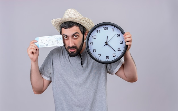 Onder de indruk jonge knappe blanke reiziger man met hoed met klok en vliegtuigticket geïsoleerd op wit met kopie ruimte
