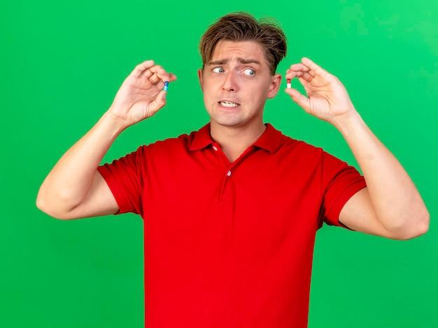 Onder de indruk jonge knappe blonde zieke man die medische capsules aan de voorkant toont, kijkend naar een van hen geïsoleerd op groene muur