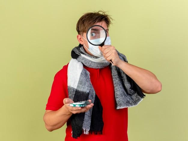 Onder de indruk jonge knappe blonde zieke man die sjaal draagt die medische pillen door vergrootglas houdt dat op olijfgroene muur met exemplaarruimte wordt geïsoleerd