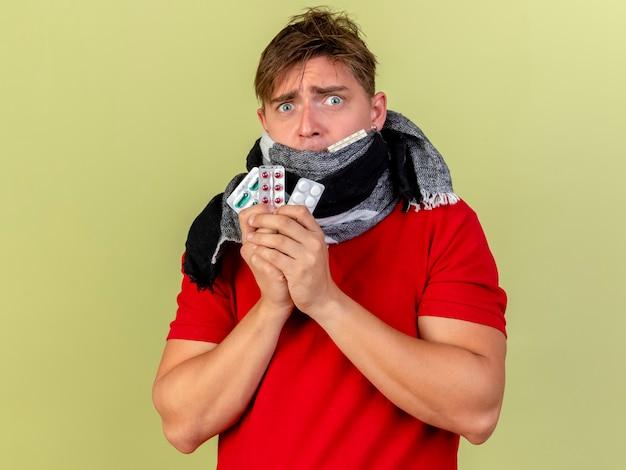 Onder de indruk jonge knappe blonde zieke man dragen sjaal thermometer bedrijf in mond en verpakkingen van medische pillen kijken camera geïsoleerd op olijfgroene achtergrond met kopie ruimte