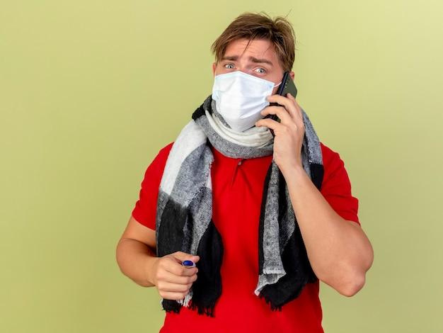 Onder de indruk jonge knappe blonde zieke man met masker en sjaal houden thermometer praten over telefoon geïsoleerd op olijfgroene muur met kopie ruimte