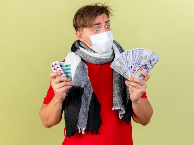 Onder de indruk jonge knappe blonde zieke man met masker houden geld en verpakkingen van medische pillen kijken naar geld geïsoleerd op olijfgroene achtergrond