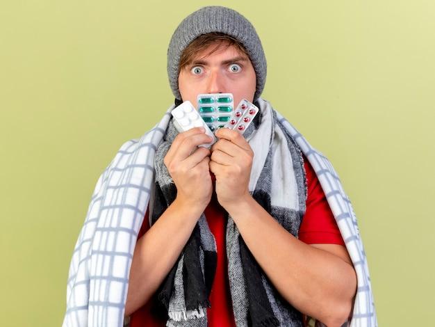 Onder de indruk jonge knappe blonde zieke man met winter muts en sjaal gewikkeld in geruite mond aanraken met verpakkingen van medische pillen kijken camera geïsoleerd op olijfgroene achtergrond