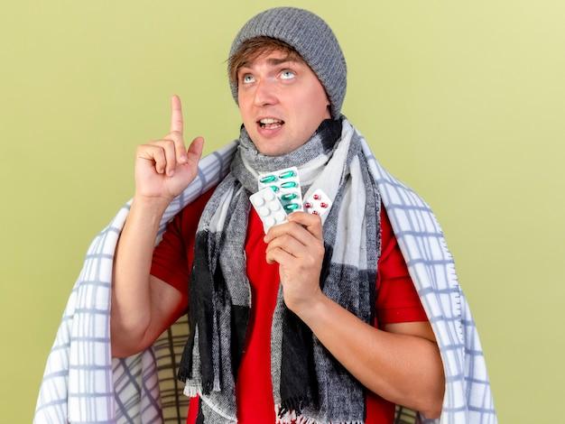 Onder de indruk jonge knappe blonde zieke man met winter muts en sjaal gewikkeld in plaid bedrijf verpakkingen van medische pillen kijken en omhoog wijzen geïsoleerd op olijfgroene muur