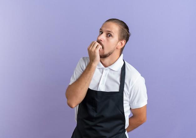 Onder de indruk jonge knappe kapper die uniform draagt dat zijn vingers bijt en hand achter rug houdt die op paars met exemplaarruimte wordt geïsoleerd