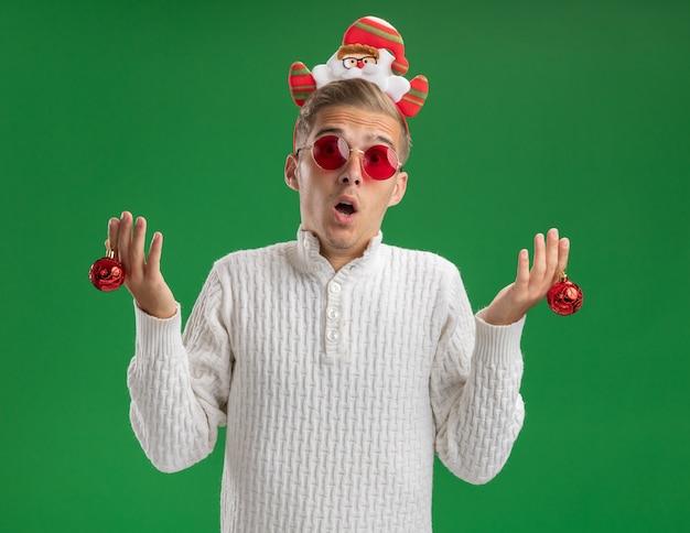 Onder de indruk jonge knappe kerel die de hoofdband van de kerstman met glazen draagt die de ballen van het kerstornament bekijkt die camera bekijkt die op groene achtergrond wordt geïsoleerd
