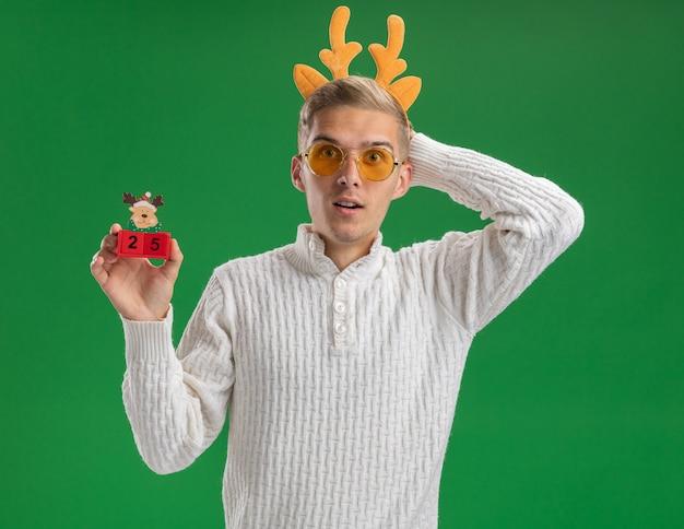 Onder de indruk jonge knappe kerel dragen rendieren gewei hoofdband met bril kerstboom speelgoed met datum kijken camera houden hand achter hoofd geïsoleerd op groene achtergrond