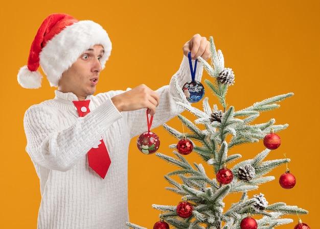 Onder de indruk jonge knappe kerel met kerstmuts en stropdas van de kerstman staande in de buurt van de kerstboom het versieren met kerst bal ornamenten kijken naar boom geïsoleerd op een oranje achtergrond