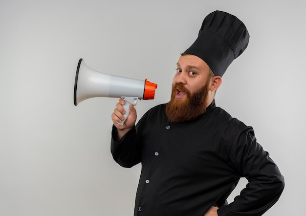 Onder de indruk jonge knappe kok in chef-kok uniform praten door spreker geïsoleerd op een witte muur white