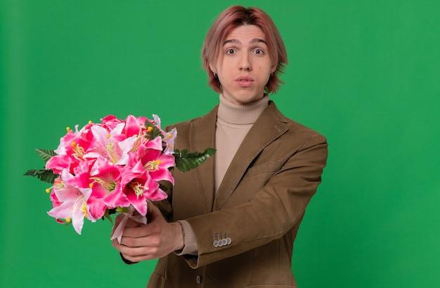 Onder de indruk jonge knappe man die een boeket bloemen uithoudt op zoek naar
