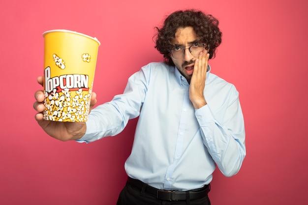 Onder de indruk jonge knappe man die een bril draagt die emmer popcorn naar voren uitstrekt en de hand op het gezicht houdt en naar de voorkant kijkt die op roze muur wordt geïsoleerd