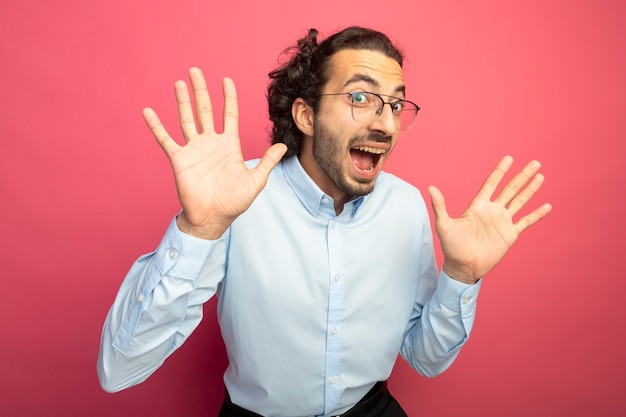 Onder de indruk jonge knappe man die een bril draagt en naar de voorkant kijkt die lege handen toont die op roze muur worden geïsoleerd