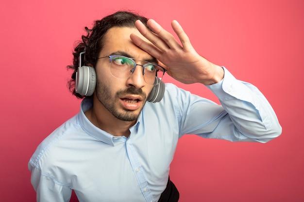 Onder de indruk jonge knappe man met bril en koptelefoon hand houden op voorhoofd kant kijken in afstand geïsoleerd op roze muur