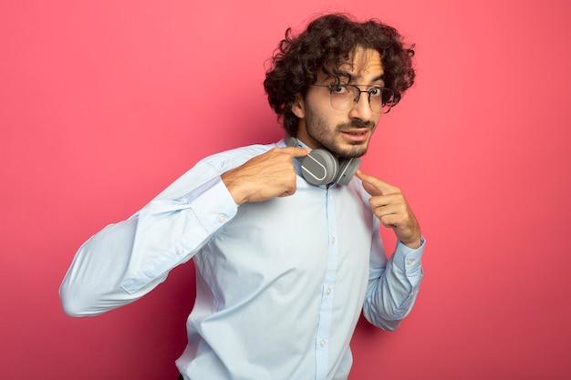 Onder de indruk jonge knappe man met bril en koptelefoon op nek kijken voorkant wijzend op koptelefoon geïsoleerd op roze muur