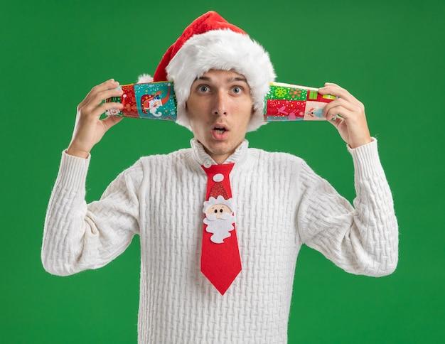 Onder de indruk jonge knappe man met kerstmuts en stropdas van de kerstman met plastic kerstbekers naast oren geïsoleerd op groene muur