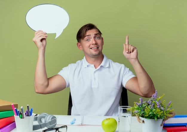 Onder de indruk jonge knappe mannelijke studentenzitting bij bureau met schoolhulpmiddelen die praatjebel houden en wijst omhoog geïsoleerd op olijfgroen