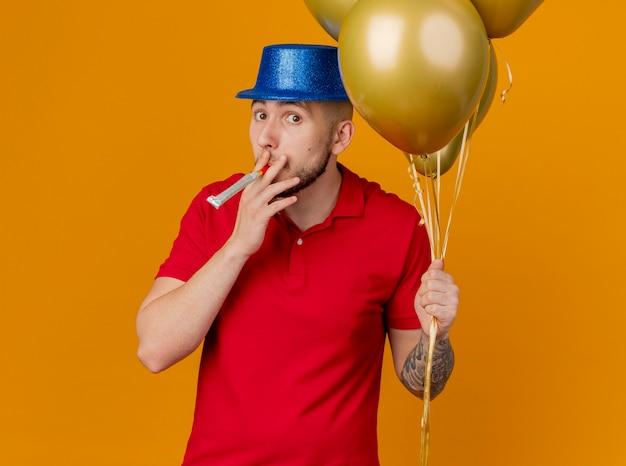 Onder de indruk jonge knappe slavische feestjongen die feestmuts draagt ?? die ballonnen houdt die kijken naar de blazende partijblazer van de camera die op een oranje achtergrond wordt geïsoleerd