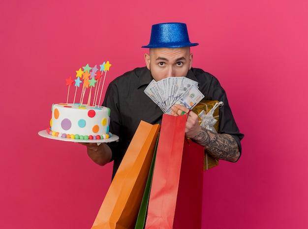 Onder de indruk jonge knappe slavische feestjongen die feestmuts draagt ?? die geld papieren zakken cadeau pack en verjaardagstaart kijkt naar camera geïsoleerd op karmozijnrode achtergrond met kopie ruimte