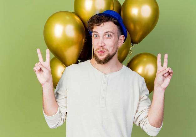 Onder de indruk jonge knappe slavische feestjongen die feestmuts draagt die zich achter ballonnen bevinden die camera bekijken die vredestekens doen die op olijfgroene achtergrond worden geïsoleerd