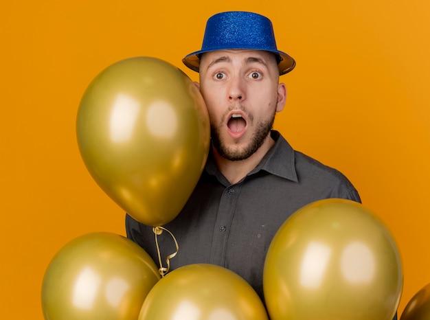 Onder de indruk jonge knappe slavische feestjongen die feestmuts draagt die zich achter ballons bevindt die camera bekijkt die op oranje achtergrond wordt geïsoleerd