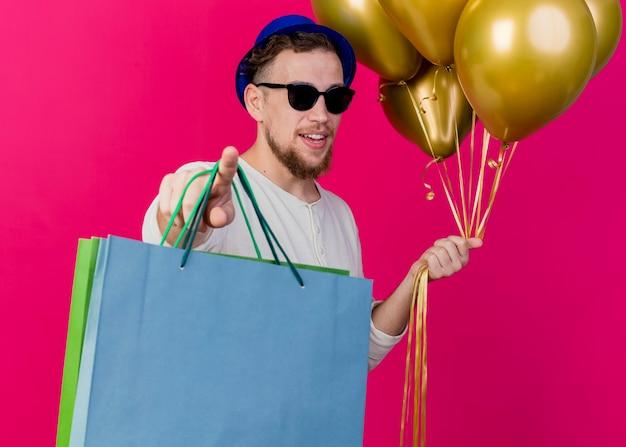 Onder de indruk jonge knappe slavische feestjongen met feestmuts en zonnebril met ballonnen en papieren zakken wijzend en kijken naar camera geïsoleerd op karmozijnrode achtergrond