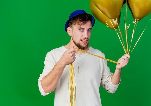 Onder de indruk jonge knappe slavische feestmens die feestmuts draagt die ballonnen houdt en camera kijkt die op groene achtergrond met exemplaarruimte wordt geïsoleerd
