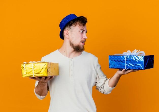 Onder de indruk jonge knappe slavische feestmens die feestmuts draagt en naar geschenkdozen kijkt die op een oranje achtergrond worden geïsoleerd